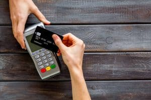 Contactless payment, paypass. Hand hold bank card near terminal on dark wooden background top down copy space