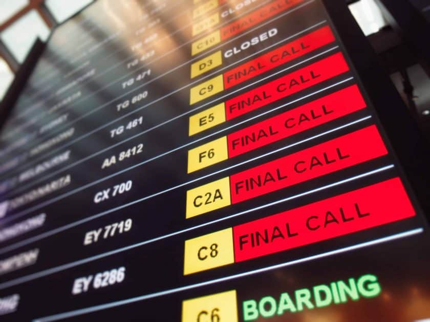 Many red sign final call flights on the departure table of an airport