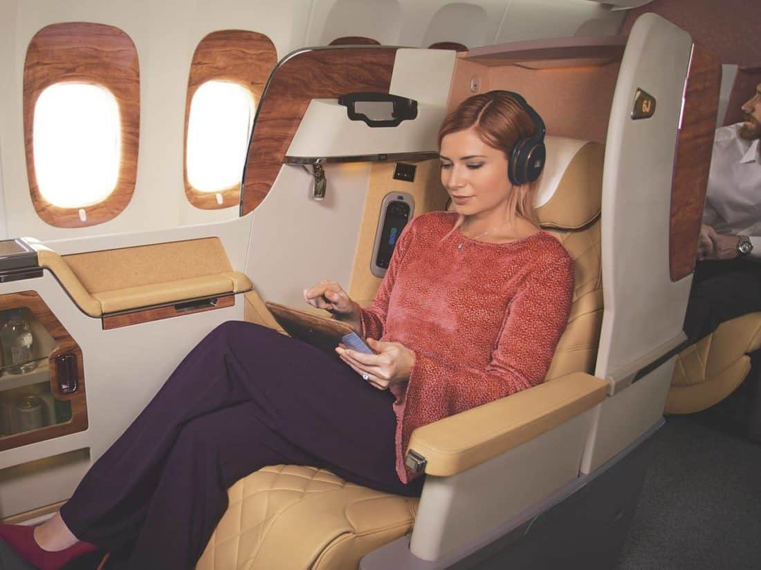 emirates woman on business class listening to music w1280x960